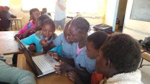 girls using donated laptop