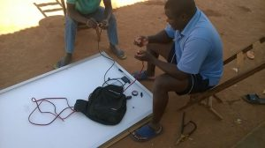 Head teacher of Dambilo sets up solar panels donated by S&C Electric
