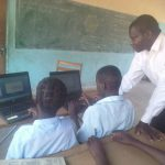 Teacher Humphrey working with Kawila pupils on donated laptops